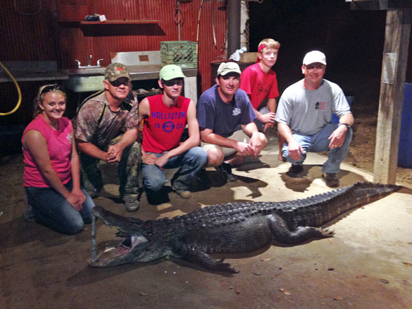 THE PRENTISS HEADLIGHT / Nick Smith of Brookhaven (pictured fourth from the left) drew a tag designated to the Southwest zone for this year's alligator hunting season. Smith claimed this 9-ft gator on September 1 using a throw hook on the Big Black River. Invited along on the hunt were LeAnne and George Griffith of Prentiss, Brandon Hughes of Columbia, Slay Acy and Kyle Smith, all of Brookhaven.