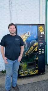Shirley Burnham / The Prentiss Headlight—Broome stands in front of the unique bait vending machine that helps fishermen get bait during business closed hours.