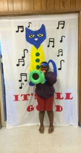 The Prentiss Headlight—At the Prentiss Library Miquelle Davis enjoys Pete, the Cat's blowup trumpet.