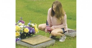 The Prentiss Headlight—Karrie Sue McPhail, a member of the Catholic Youth Organization at St. Peter's Catholic Church, places a flag on the grave of a JDC Veteran. Flags were placed on all Veterans' graves in Carson & Bassfield.