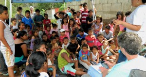 The Prentiss Headlight / Mary Lou Garner tells the Bible story through an interpreter at the outdoor VBS held by the Whitesand Team members.