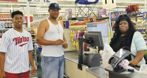 The Prentiss Headlight  / The retail food industry is one of the largest who stay open on Labor Day to accommodate the public. We thank the workers of our local store for their service to us.6-year employee of Ramey's Grocery in Prentiss Larondia Hathorne checks out groceries for Frederick Warner and nephew Keion Gray.